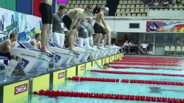 Swimmers jump into water in swimming pool — Stock Video