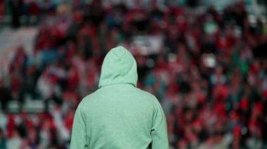 Football fan in hood against tribunes — Stock Video
