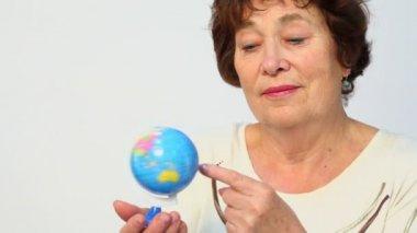 Senior woman holds earth miniature — Stock Video