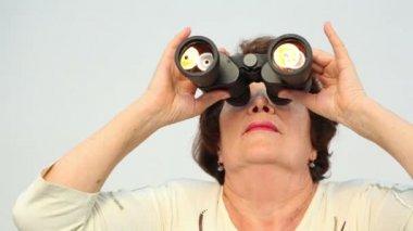 Old woman looks in binoculars — Stock Video