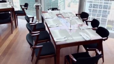 Chairs at table with tableware near window — Stok video