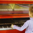 Little girl plays red piano — Stock Video #65691243