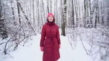 Woman in warm clothes walks in park — Stockvideo
