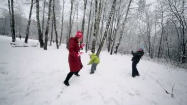 Woman plays snowballs with her kids — Stock Video