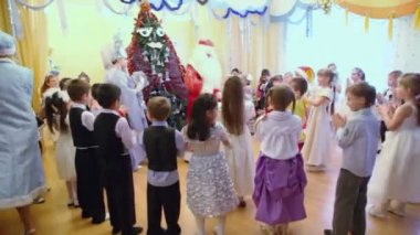 Children stand around fir tree — Stock Video
