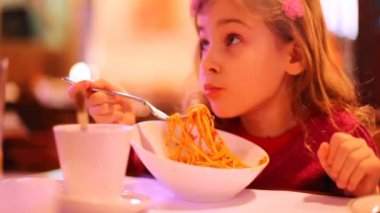 Adorable little girl eating noodles — Stock Video