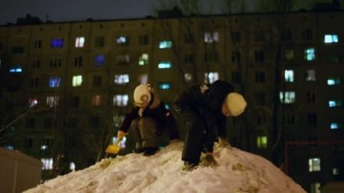 Girl and brother on snowbank — Stock Video