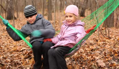 Boy and girl swinging in hammok — Stockvideo