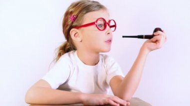 Little girl simulates pipe smoking — Stock Video