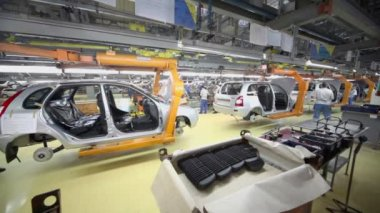 Workers assemble automobiles on conveyor — Stock Video