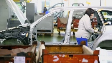 Woman assemble cars on conveyer — Stock Video