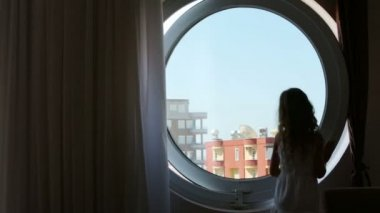 Girl closes round window — Vídeo stock