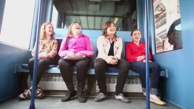 Four girls sit in coach of train — Stock Video
