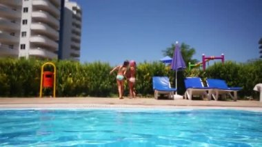 Two little girlfriends jump into pool — Stock Video