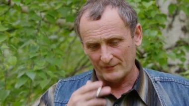 Elderly man smokes cigarette — Stock Video