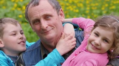 Grandchildren hug grandfather — Vídeo de Stock
