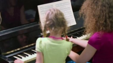 Little girl and mother play piano — Stock Video