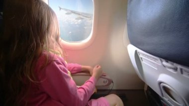 Little girl looks out window in aircraft — ストックビデオ