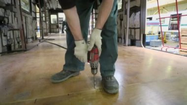 Worker drills wooden floor — Stock Video