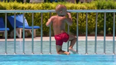 Little boy gets out of pool — Stock Video