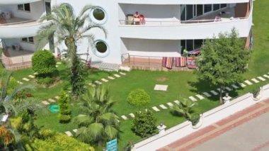 Grön gräsmatta nära hotel — Stockvideo