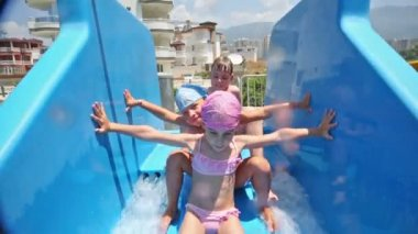Girls and boy rolls on blue waterslide — Stock Video