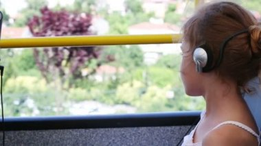 Girl in headphones riding on sightseeing bus — Stock Video