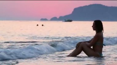 Young woman sits in profile on sand — Stock Video