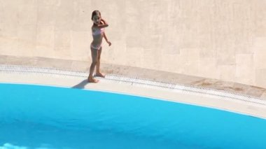Little girl climbs out of pool — Stock Video