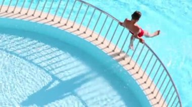 Boy sits on handrail at pool — Stockvideo