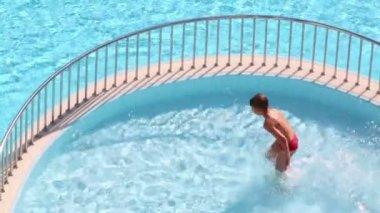 Little boy runs in pool — Stock Video