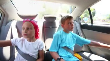Children sit fastened by seat belts — Stock Video