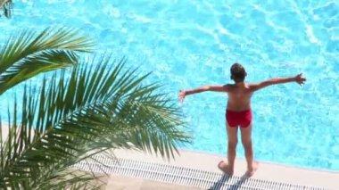 Boy takes sunbathe on edge of pool — Stock Video