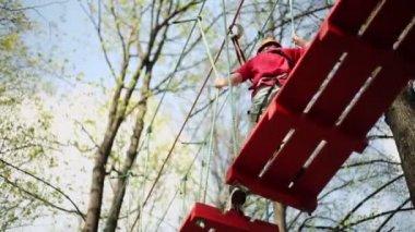 Young climber walks on wooden platform — Vídeo de stock