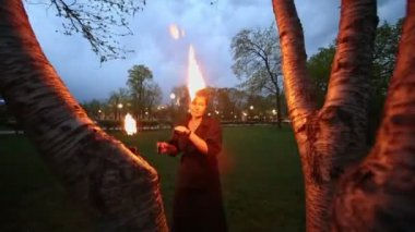 Woman in black rotates poi with flame — Stock Video