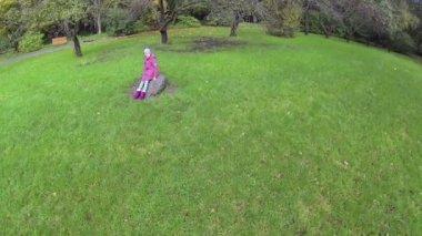 Beautiful little girl sitting on rock — Stockvideo