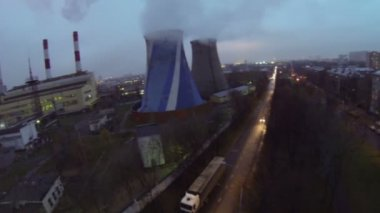 Street traffic near power plant with tubes which emit smoke — Stock Video