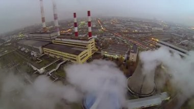 Cityscape with power plant tubes which emit smoke and steam — Stock Video