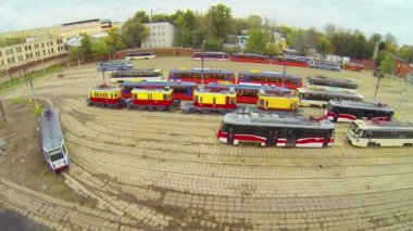 Bright trams in city depot in autumn day, aerial view — Stock Video