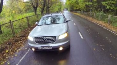 Silvery car with lights on driving slowly — Vidéo