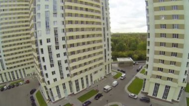 People and car moving in parking lot of building complex — Vidéo