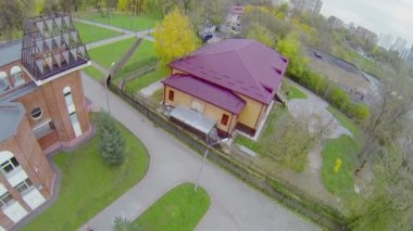 Wooden house with magenta roof and round paved yard — Stock Video