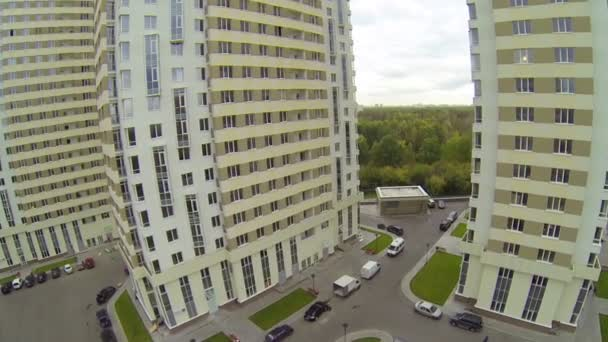 People and car moving in parking lot of building complex — Vídeo de stock