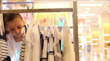 Little girl looks over hangers with clothing — Stockvideo