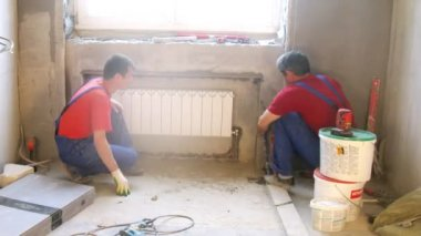 Workers fixing pipes of heating radiator — ストックビデオ
