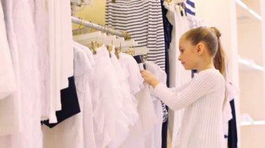 Girl chooses clothes in shop — Stockvideo