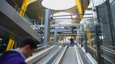 Travelers ride by escalator in Madrid Barajas Airport — Stock Video
