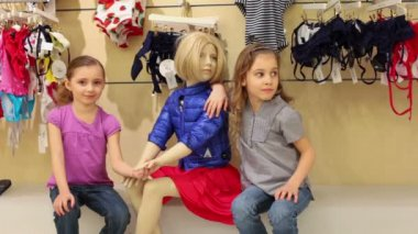 Two girls posing next to mannequin — Stockvideo