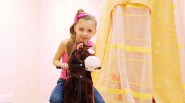 Little girl swinging on rocking horse — Stock Video