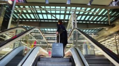 Woman with luggage rises on escalator — Stock Video